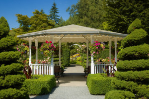 Charming white gazebo or summerhouse in lovely garden